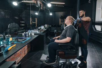 tail shaving/ Barber cutting in barbershop.  Hairdresser cuts the tail of long hair to the client.