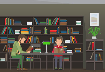 Two Boys Sit at Table and Read Books in Library