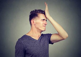 Man slapping hand on head having regrets