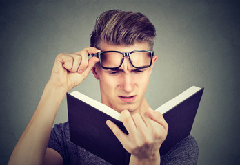 Young man with glasses suffering from eyestrain reading a book having vision problems