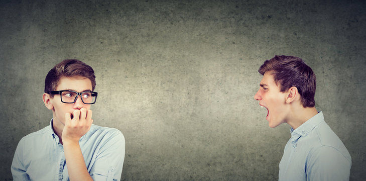 Split personality. Angry young man screaming at scared anxious himself