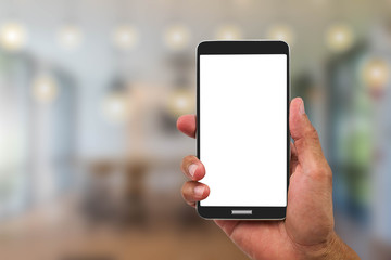 Man's hand holding blank white screen mobile phone on blurred cafe background