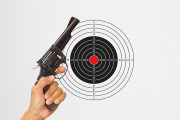 Hand holding black gun with shooting target background