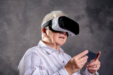 gray hairy elderly woman using virtual reality glasses