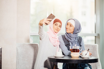 two happy young muslim woman take self portrait with handphone at cafe
