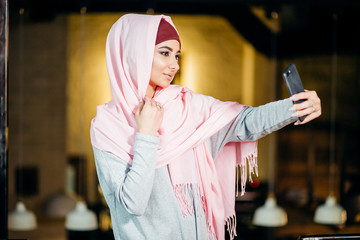 Arabian muslim woman taking selfie with phone in cafe