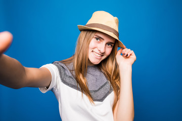 Trendy beautiful hipster girl taking selfie with mobile phone against a blue wall.