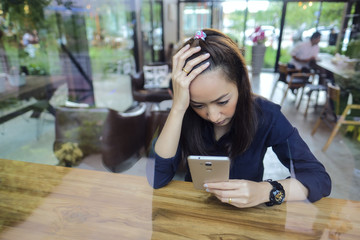 Business Woman sad reading message in mobile phone with sit in a coffee shop in a evening time by sit beside glass
