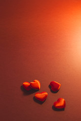 Close-up of small red velvet hearts on red background. Concept of a romantic love gift for couples, valentines day, marriages or birthdays.