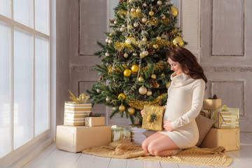 Pregnant woman happy at home decorative christmas tree with gifts and toys background