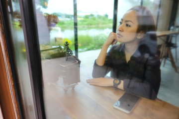 alone woman sit in coffee shop beside windows glass is steam with lonely emotional