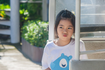 Shoot Asian little cute girl siting in goft car and thinking something.