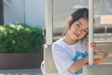 Shoot Asian little cute girl siting in goft car and smiling.