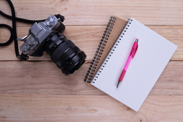 Notebook with pen and camera on wooden background