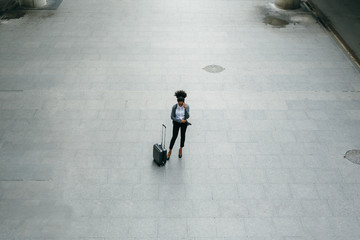 High angle view of young businesswoman standing at airport terminal with a suitcase and talking on mobile phone.
