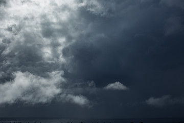 Dramatic dark storm clouds over the ocean water with bright spot of light