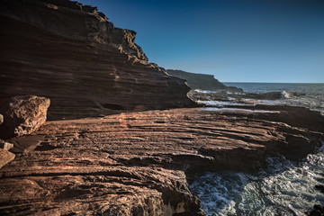 Sharp shapes, volcanic beach shorline, wind shaped rocks and stones, Aeolian process in wild nature, ocean water with waves