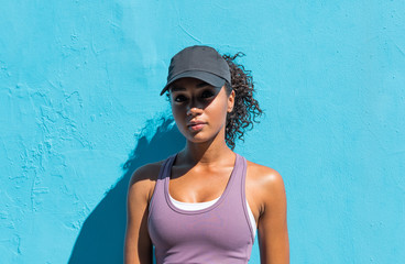 Portrait of woman in sportswear and cap outdoors Wall mural