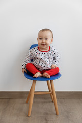 Happy baby sitting on kids chair