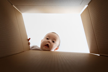 Funny face of baby looking down through cardboard box