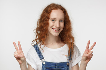 Indoor portrait of redhead girl isolated on gray background in jean jumpsuit with optimistic smile, showing victory sign with both hands, looking friendly and willing to welcome and communicate