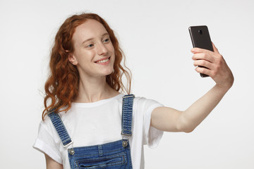 Portrait of young pretty redhead girl standing against gray background using smartphone to take selfie pictures and smiling