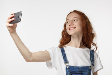 Photo of beautiful young redhead female isolated on grey background, stretching arm with smartphone to take selfie picture to share it in social networks