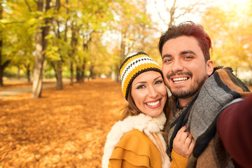 Beautiful couple taking a selfie at a park in autumn