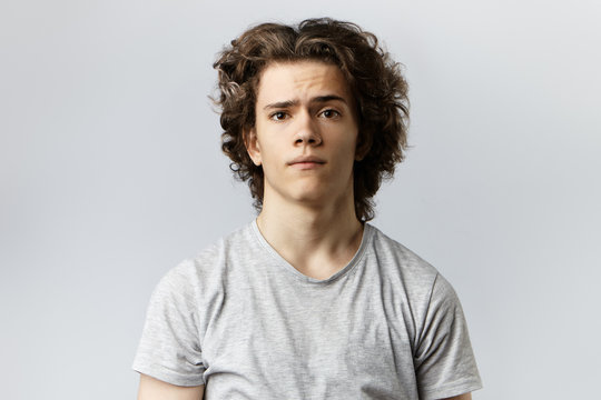 Casually dressed college student in grey t-shirt posing in studio with worried frustrated look feeling nervous before exams. Human facial expressions, emotions, reaction, life perception and feelings
