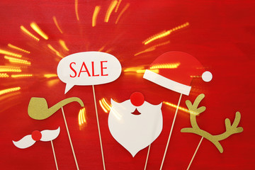 Christmas holiday shopping concept. Santa claus red and beard hat on red wooden background