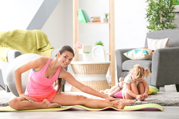 Beautiful young woman with little daughter training at home