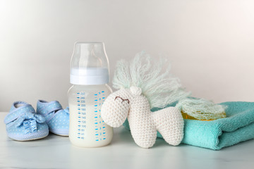 Composition with feeding bottle of baby milk formula on table