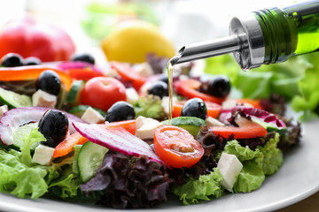 Pouring olive oil onto plate with healthy salad in kitchen