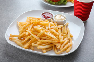 Plate with yummy french fries and sauces in small bowls on table