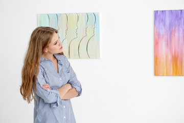 Young woman looking at painting in art gallery