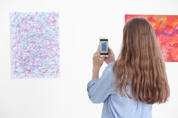 Young woman taking picture of painting in art gallery