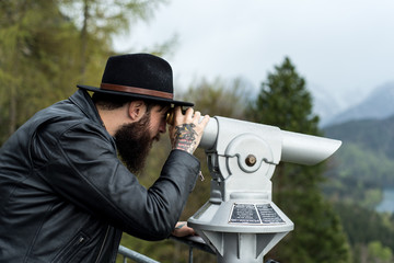 Cool Hipster observes scenic mountain scenery with a spy glass