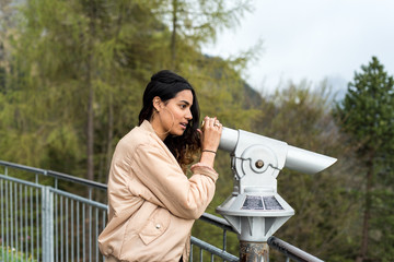 Cool Hipster girl observes scenic mountain scenery with a spy glass