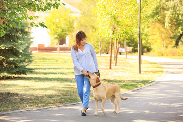 Mature woman walking her dog in park