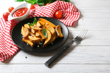 Plate with cooked sweet potato on wooden table