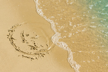 Children's drawing on a sandy sea beach. Smiling face drawn on yellow sand