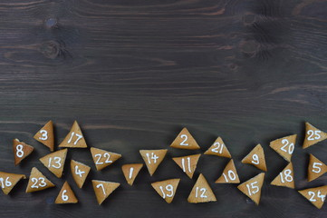 border of 25 numbered advent cookies on brown wood with copy space above