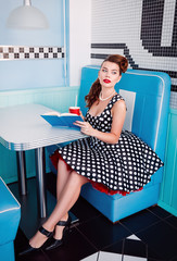 Retro (vintage) portrait of pretty young girl sitting in cafe with book and beverage. Pin up style portrait of young girl in dress