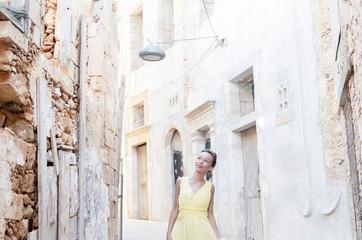 Happy woman walking through narrow street
