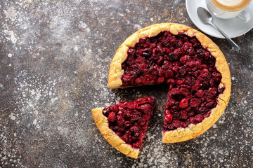 Pie with a cherry on the table with a cup of coffee