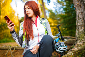 Photo of happy woman with cell phone in autumn forest