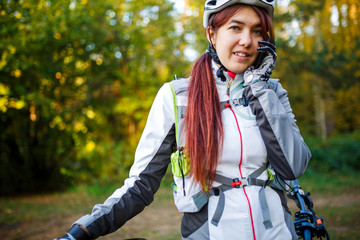 Sports girl in bicycle helmet talking on phone in autumn forest