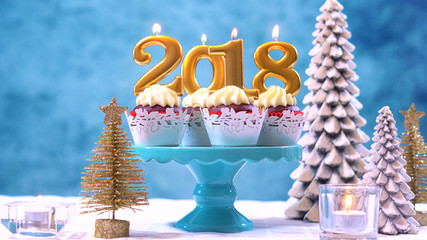 Happy New Year 2018 cupcakes on a modern stylish, festive, blue gold and white Winter theme table setting, close up with copy space.