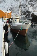 Snow covered harbor-Nusfjord fishing village-wooden fishing boat moored. Flakstadoya-Lofoten-Norway. 0481