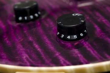 Volume and tone knobs on purple electric guitar